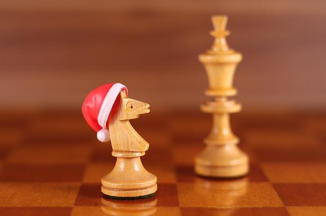 Un cavallo della scacchiera con indosso un cappello di Babbo Natale per i giochi da Tavola da giocare a Natake