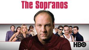 Tony Soprano in primo piano sotto la scritta/brand The Sopranos in secondo piano la Famiglia