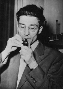 Foto di Cesare Pavese che si prepara a fumare la pipa