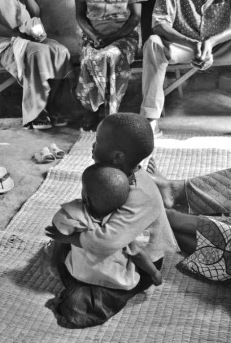 Due bambini rwandesi, seduti su un pagliericcio